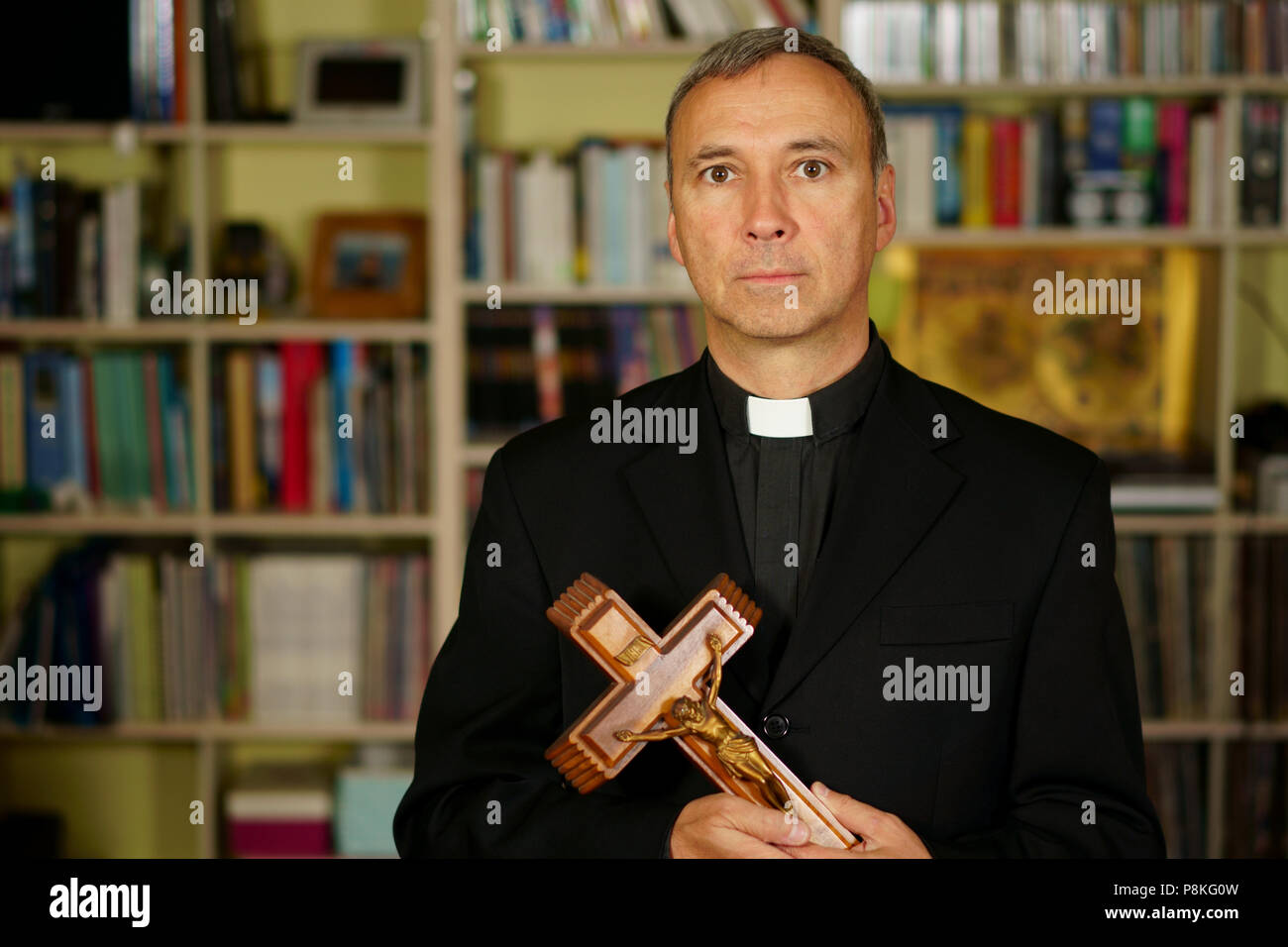 A good looking serious catholic priest is showing a crucifix. He seriously looks at us with interest, pensiveness and proselytising. - Stock Image