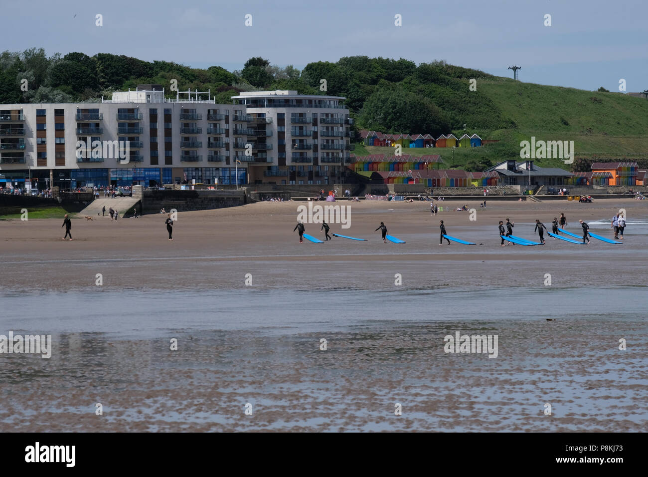 Surf boarding lessons for school or group of children on North Bay beach, Scarborough - Stock Image