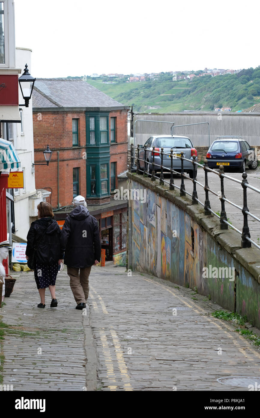 Elderly couple walking down the steep drop of Bland's Cliff,Scarborough,UK past the shops and street art to the sea front in the distance Stock Photo