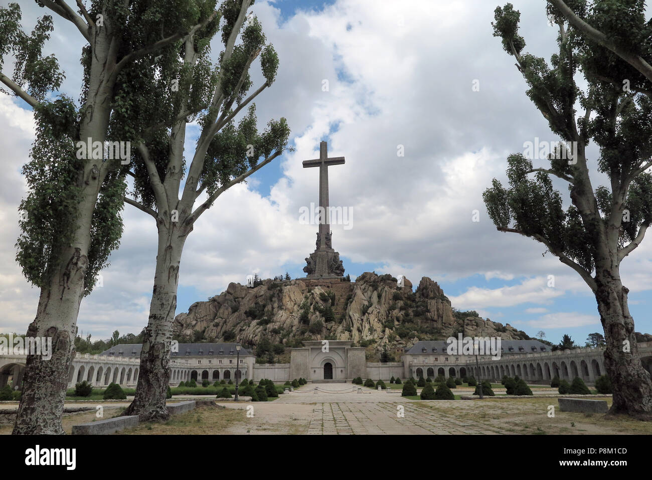 FILED - 05 July 2018, Spain, El Escorial: A 155 metres high and 44 metres wide concrete cross stands on the top of the Risco de la Nava behind the Benedictine abbey in the Valle de los Caidos (Valley of the Fallen). Inside the monument next to Cuelgamuros near El Escorial in the Sierra de Guadarrama lies the tomb of Spanish dictator Francisco Franco and the founder of the fascist movement Falange, José Antonio Primo de Rivera. It is known as one of the largest newer mausoleums of the world and the most important architectural symbol of Franco's dictatorship. Next to the basilica, in a shrine, Stock Photo