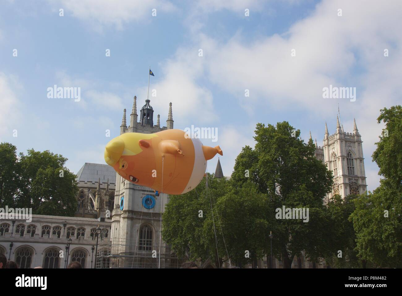 London, UK. 13th July, 2018. Trump baby balloon flying over Parliament Square, Westminster, London, in protest of President Donald Trump's visit to the UK. The balloon campaign raised almost £18,000 and was given permission for Mayor of London Sadiq Khan to fly. Credit: Dimple Patel/Alamy Live News - Stock Image