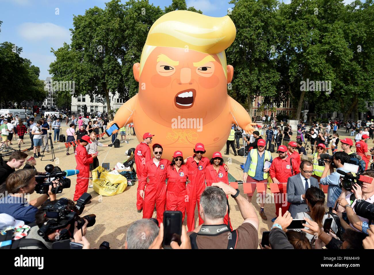 A six-metre balloon depicting as US President Donald Trump a nappy-clad orange baby over Parliament Square during the president's UK visit.  Credit: Finnbarr Webster/Alamy Live News - Stock Image
