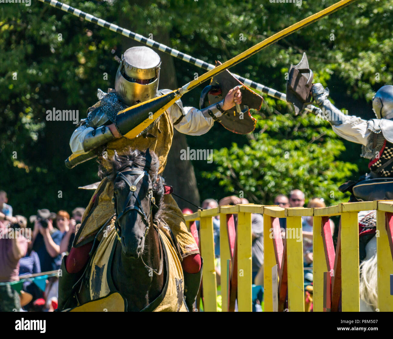 Medieval jousting, Linlithgow Palace, Scotland, UK. HES summer entertainment by Les Amis D'Onno equine stunt team. Knights on horses joust with lances - Stock Image