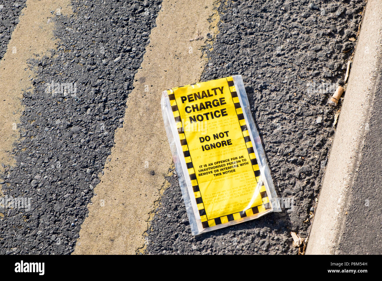 Discarded penalty charge notice. Parking fine removed from vehicle and thrown on a road with double yellow lines, Nottinghamshire, England, UK - Stock Image