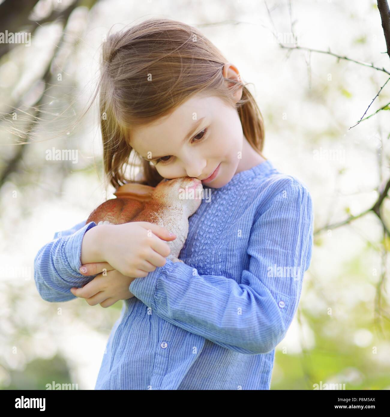 Adorable little girl holding easter bunny in blooming cherry garden on  beautiful spring day - Stock