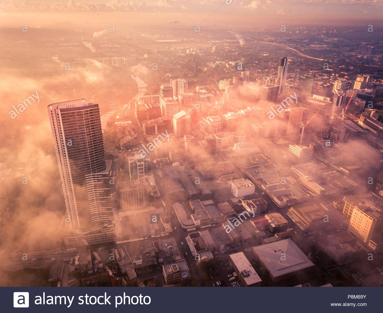Drone aerial view of a misty foggy morning in a bustling downtown central business district. Urban city setting at dawn. - Stock Image