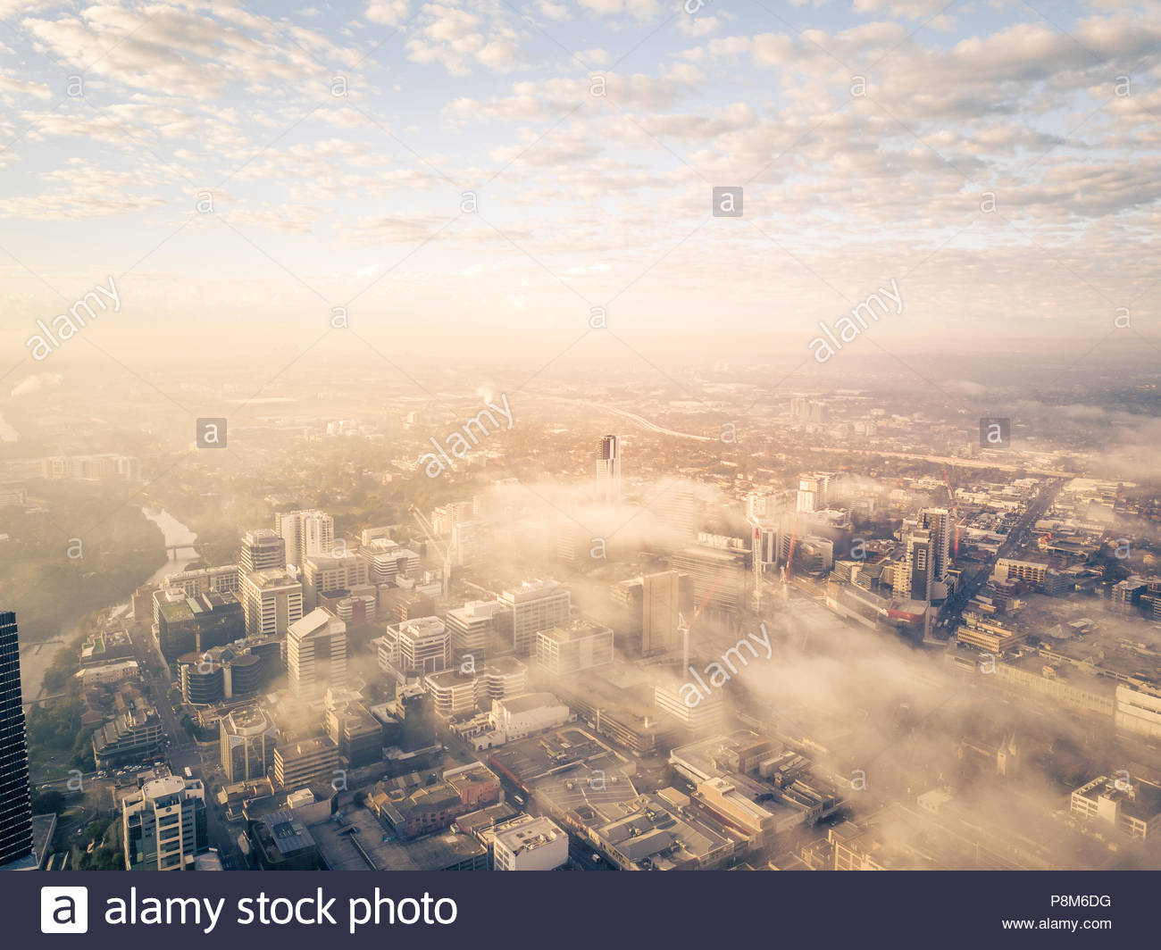 Drone aerial view of a misty foggy morning in a bustling downtown central business district - Stock Image