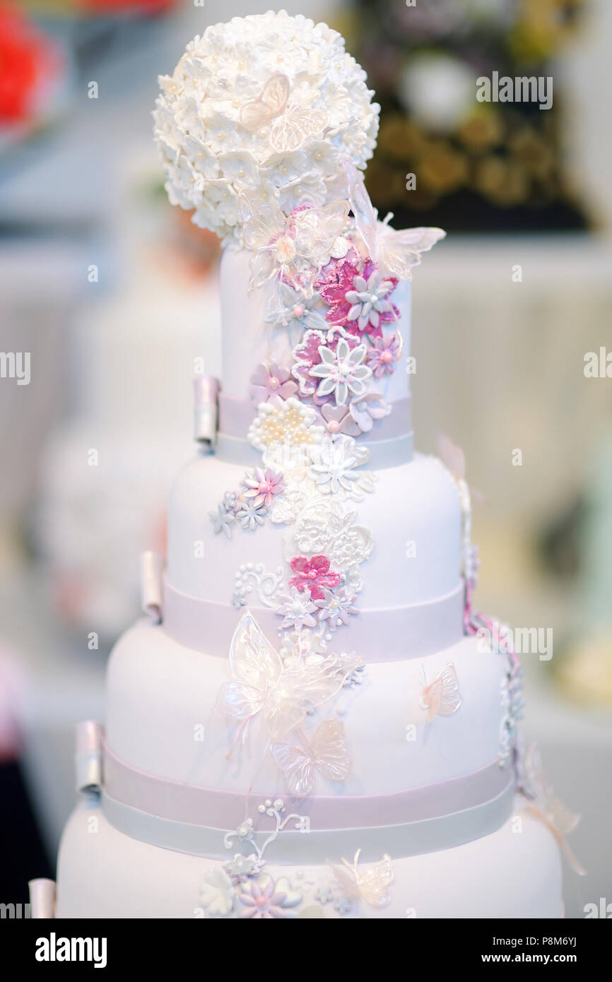 Fancy delicious white wedding cake decorated with flowers and ...
