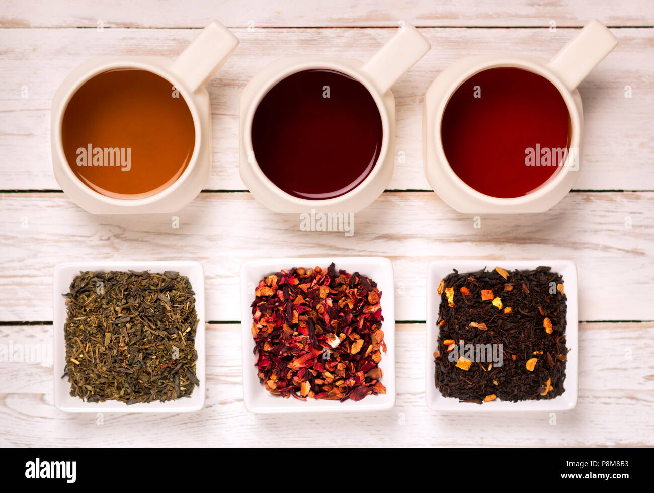From above various kind of tea in mugs and small square plates with dry tea on white wooden background & From above various kind of tea in mugs and small square plates with ...