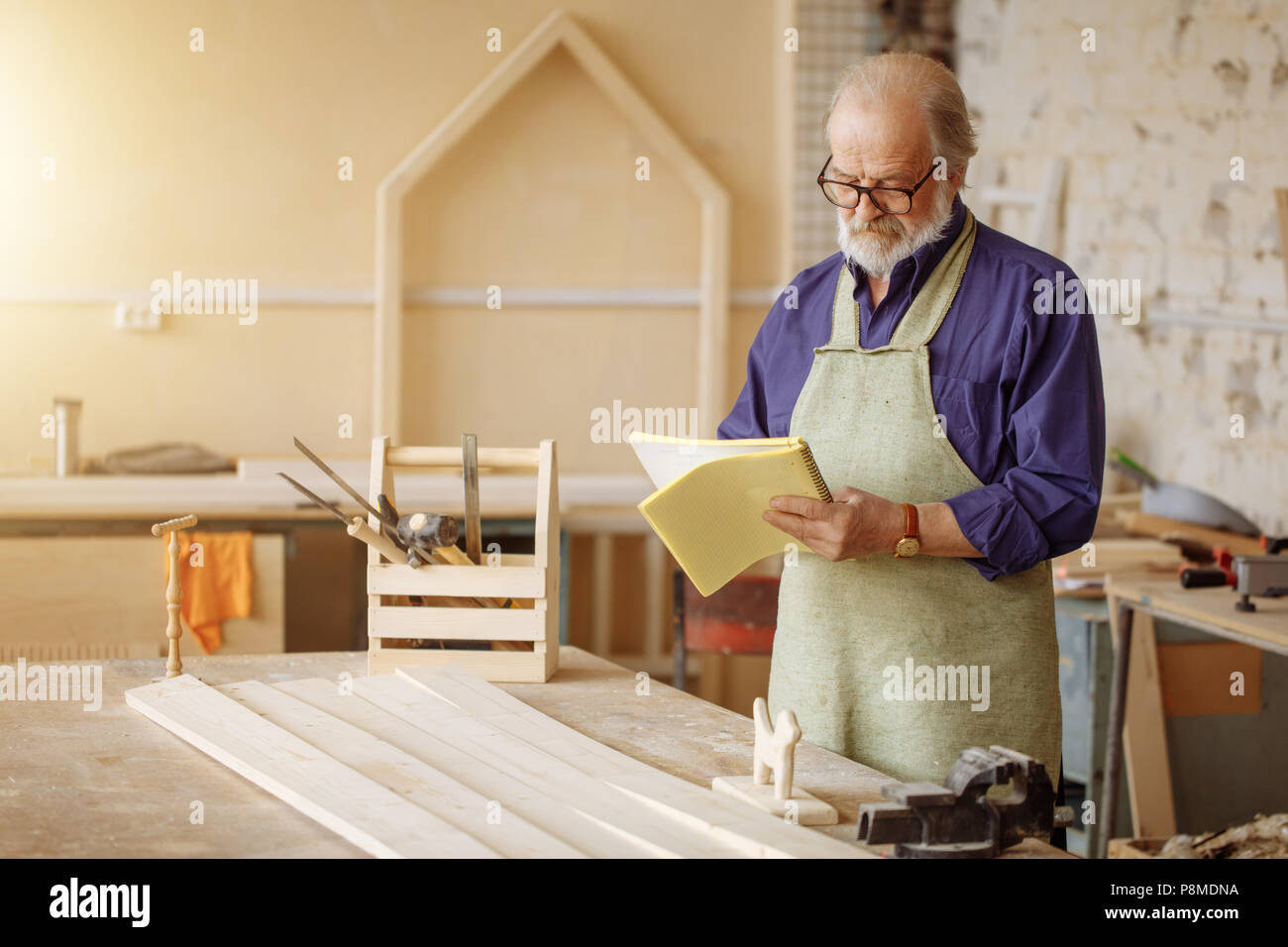 old thoughtful woodworker read manual. learn to work with wood. learn the manual - Stock Image