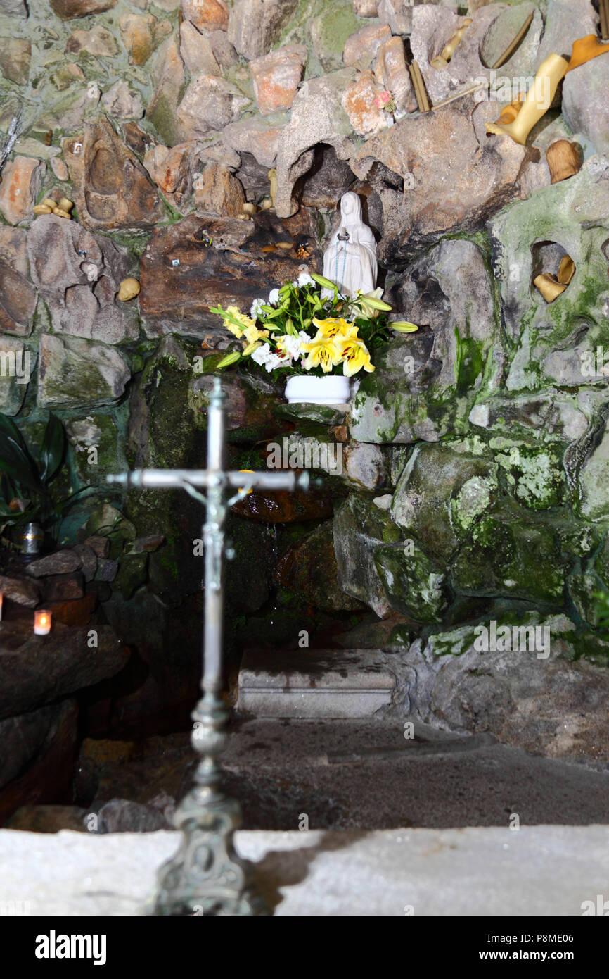 Virgen of Lourdes statue, spring and wax body parts in grotto on Monte do Calvario, Vila Praia de Ancora, Minho Province, northern Portugal - Stock Image