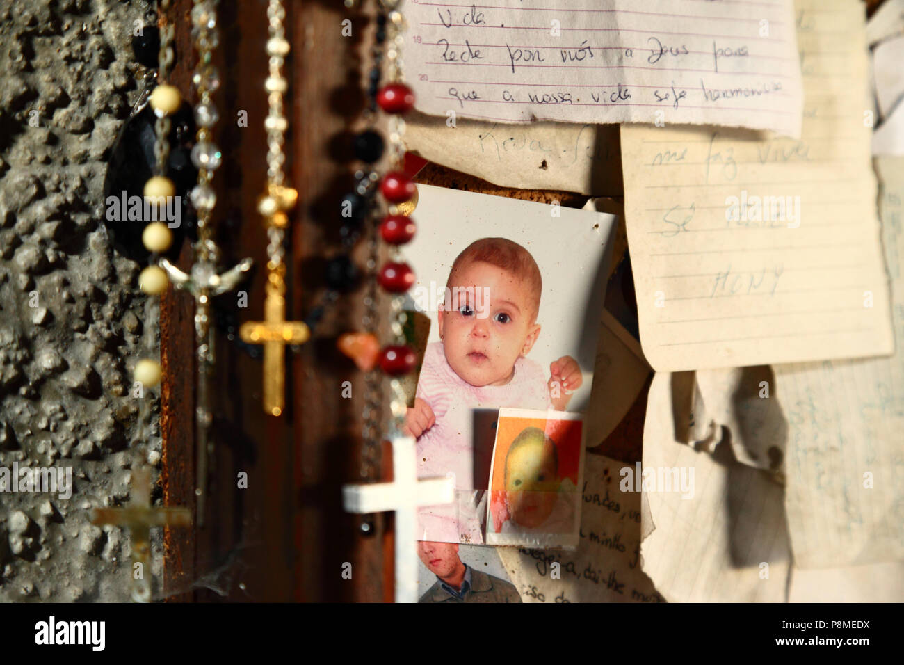 Letters of thanks, rosaries and photos of a baby in Virgen of Lourdes grotto on Monte do Calvario, Vila Praia de Ancora, Minho Province, northern Port - Stock Image