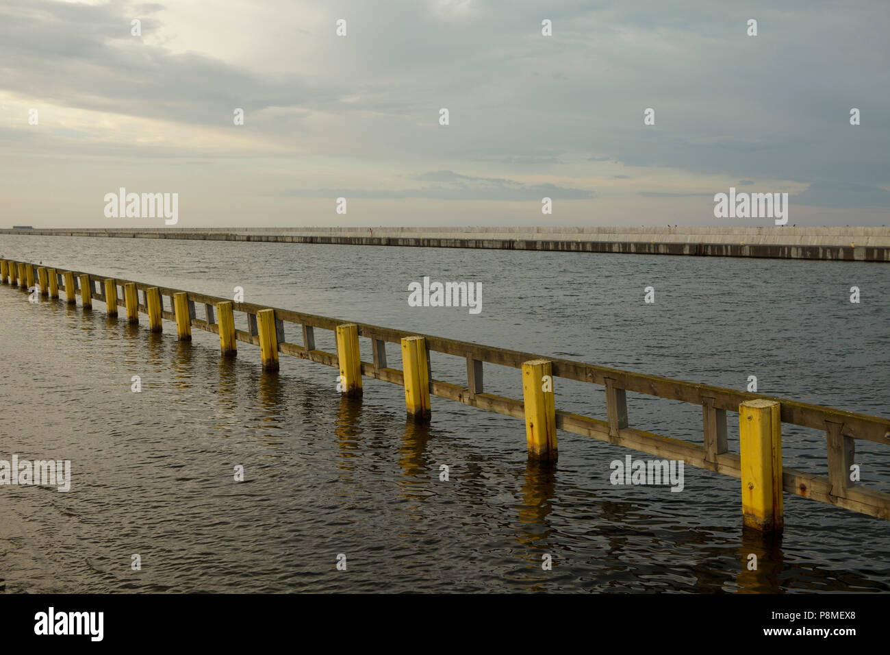 yellow pales in harbour, wide angle, cloudy, summer evening Stock Photo
