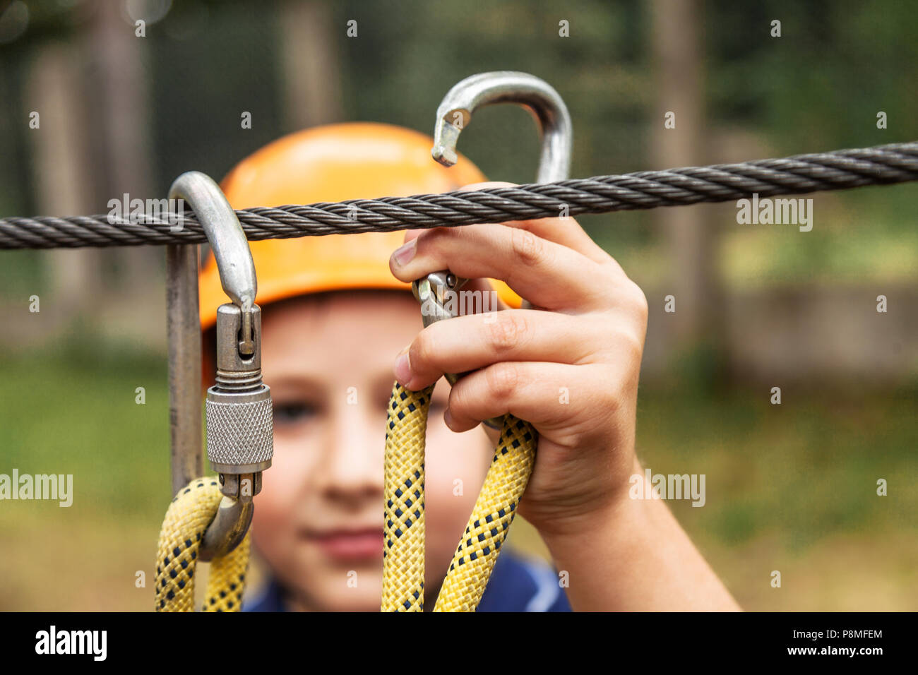 The boy fastens the carbine for the safety rope - Stock Image