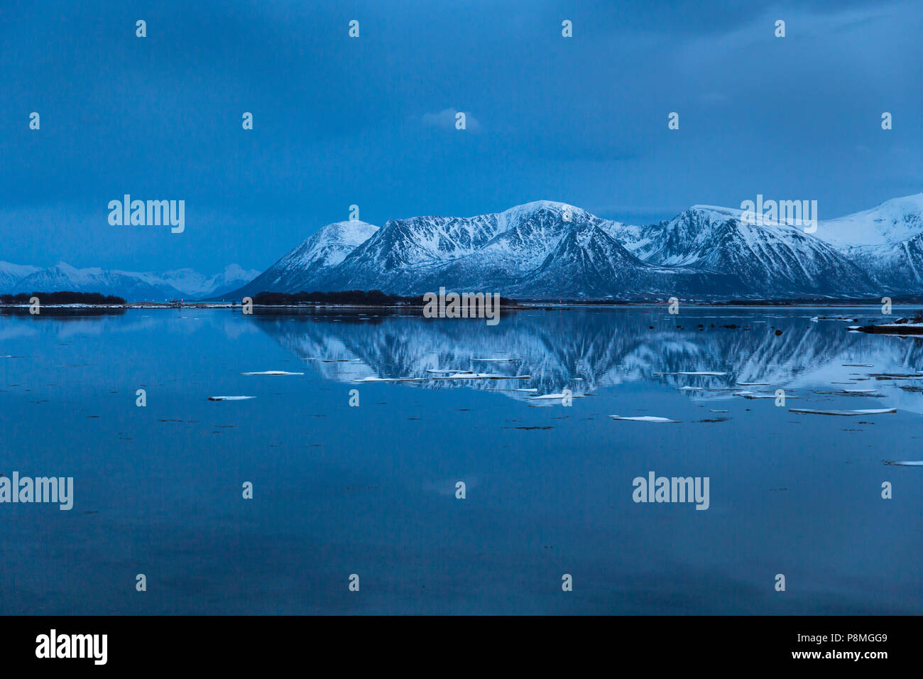 Snow-covered mountains reflecting in a lake after sunset - Stock Image