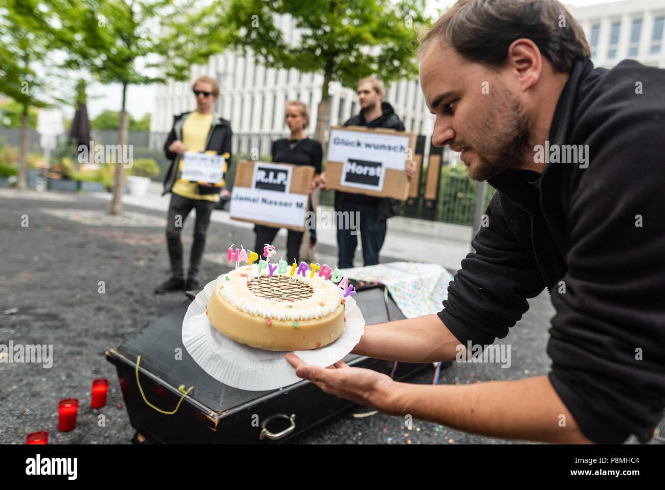 An Activist Seen Holding A Birthday Cake For Horst Seehofer
