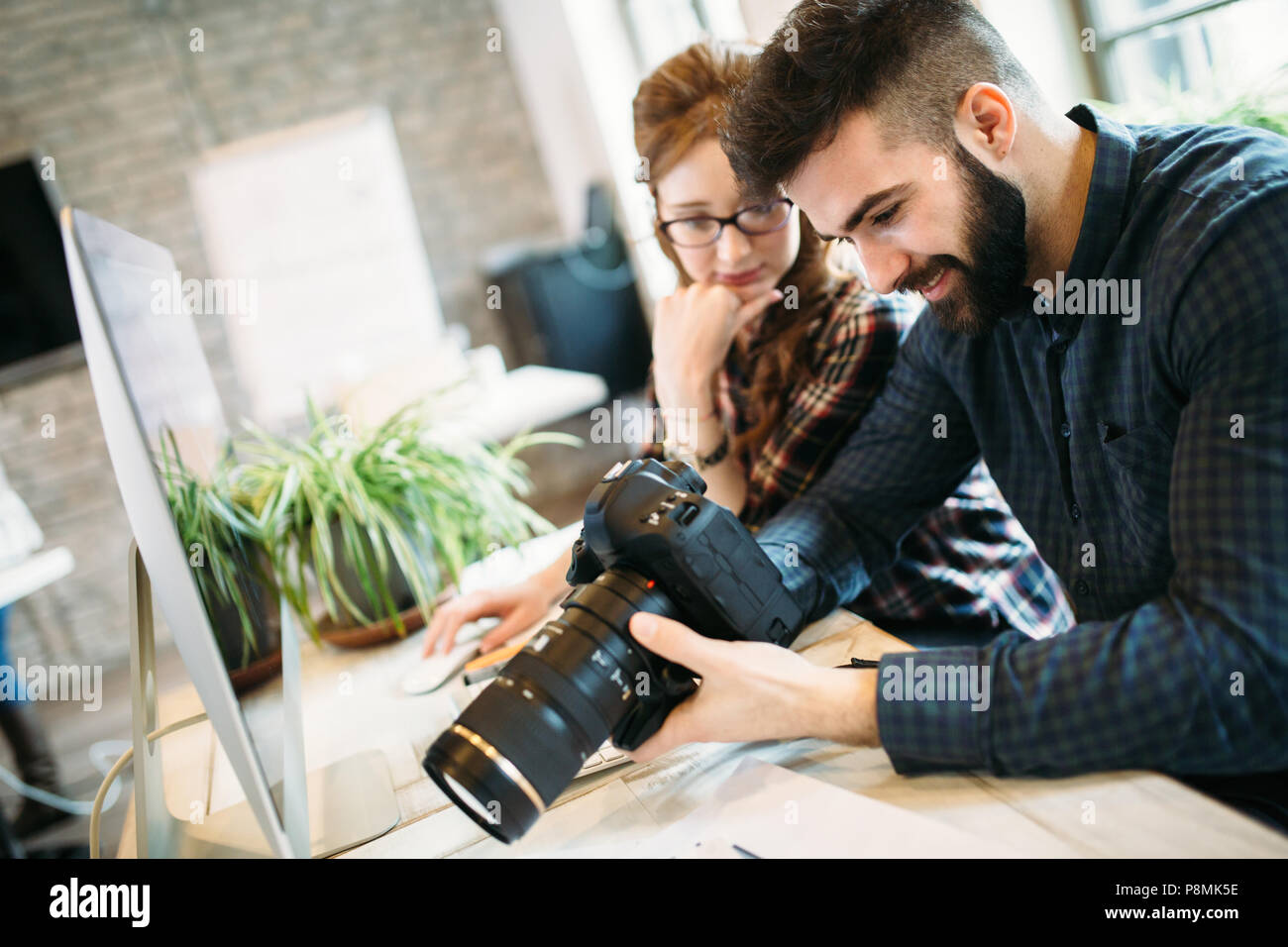 Two young designers working in modern office - Stock Image