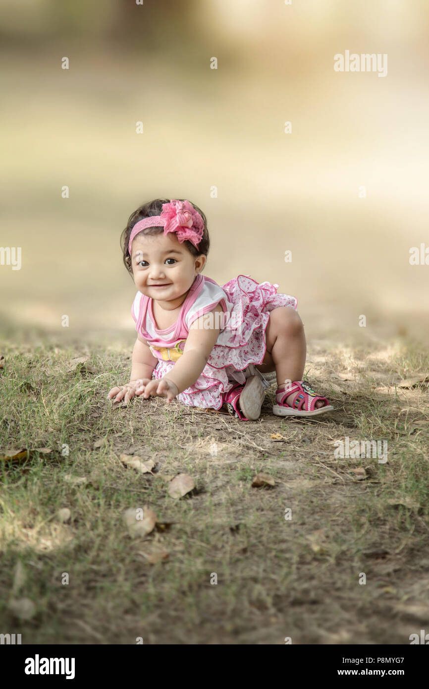 Selective focus of Happy 6 month Indian/Asian little kid wearing pink dress crawling on the grass and playing. shallow depth of field. - Stock Image