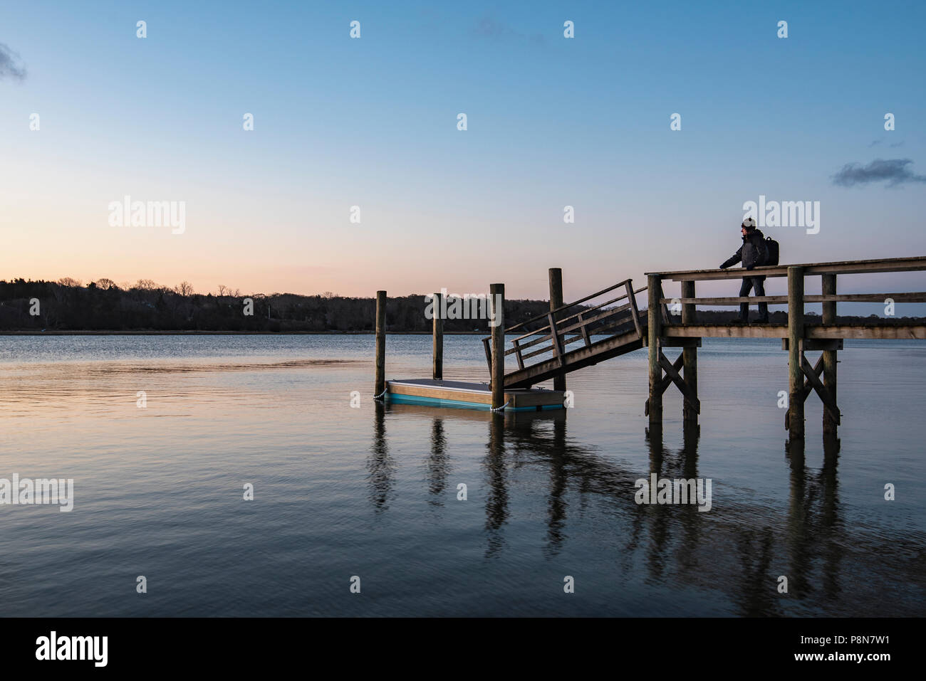 MAN STANDING ON JETTY AT DAWN, CAPE COD, MA, USA - Stock Image