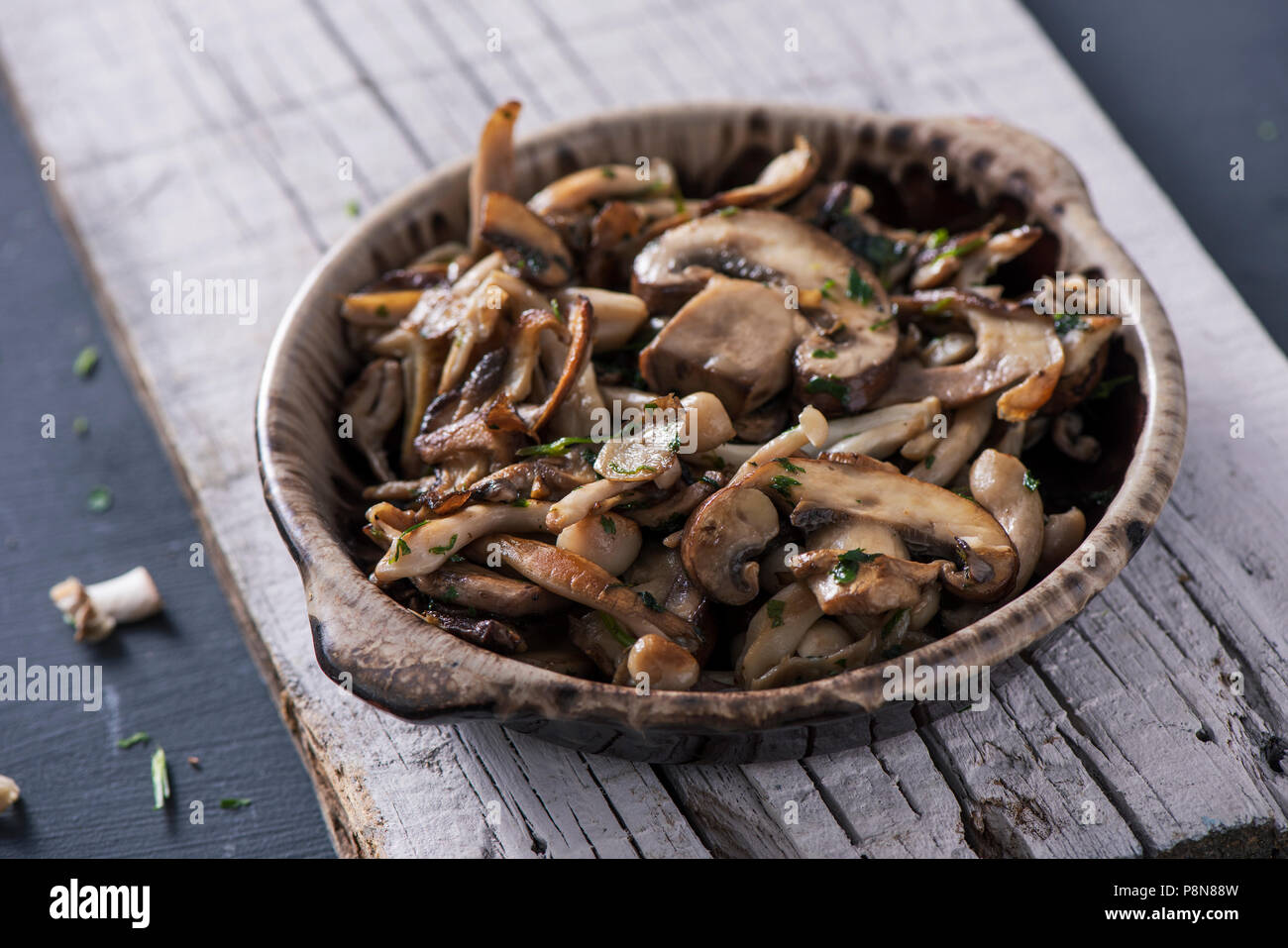 closeup of a brown earthenware bowl with some cooked mixed mushrooms, such as common mushrooms, oyster mushrooms or shiitake, on a white rustic wooden - Stock Image