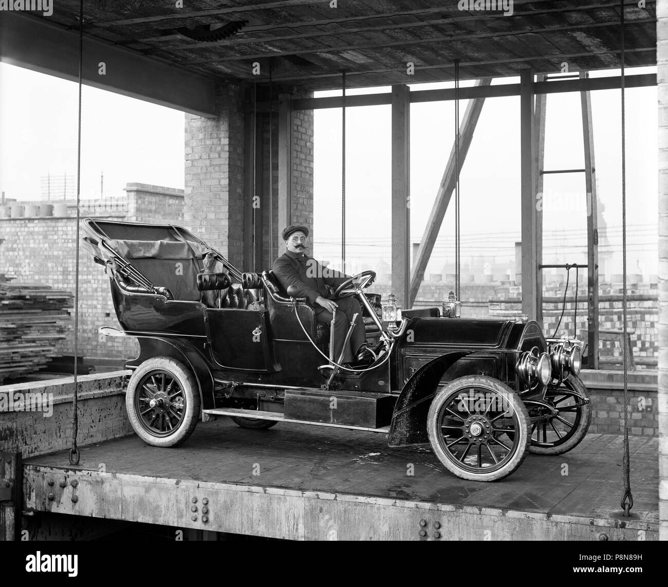 Car lift at Mitchell Motors Company, 114 Wardour Street, Westminster, London, 1907. An early motor car, with a chauffeur in the driver's seat on a car - Stock Image