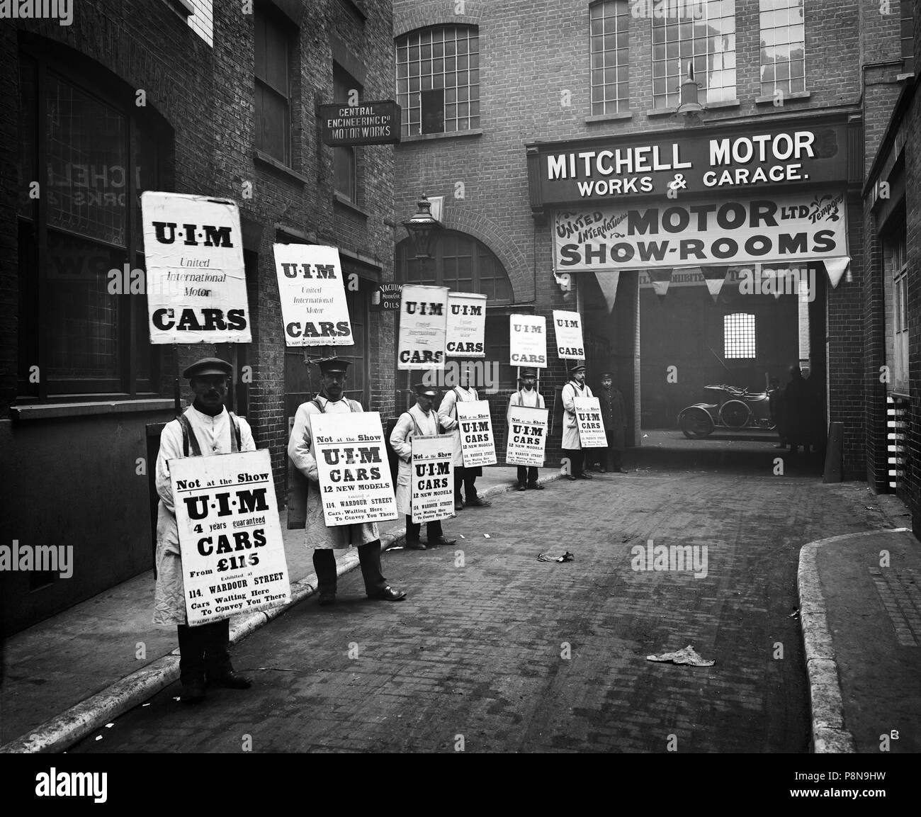 Sandwich board men advertising outside Mitchell Motors, 114 Wardour Street, London, 1910. A line of men wearing sandwich boards advertising United Int - Stock Image