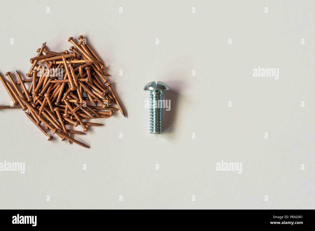 Close up of a group of bronze nails and a single metal screw. - Stock Image