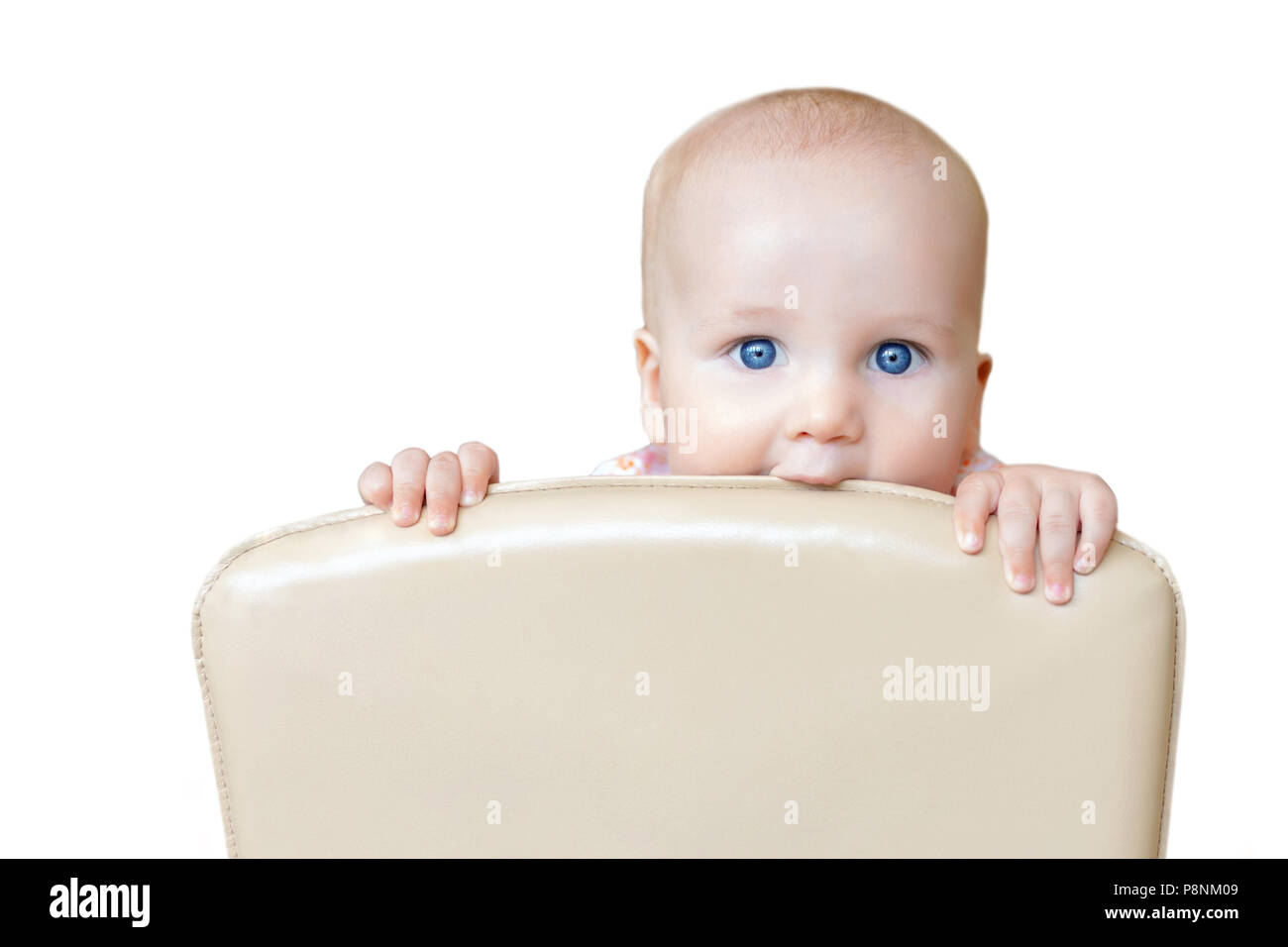 Little cute baby boy with big blue eyes biting back of chair isolated on white . Fun child peeking out chairback. Infant kid during teething. Happy ch Stock Photo