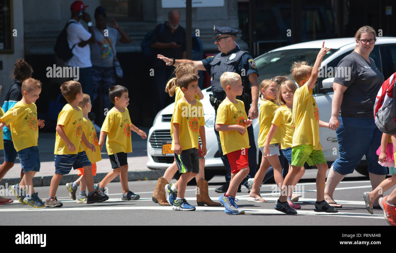 Policeman crosses children, activities and people during Wilkes Barre PA's. Thursday farmers market on the public square in central city July 2018 Stock Photo