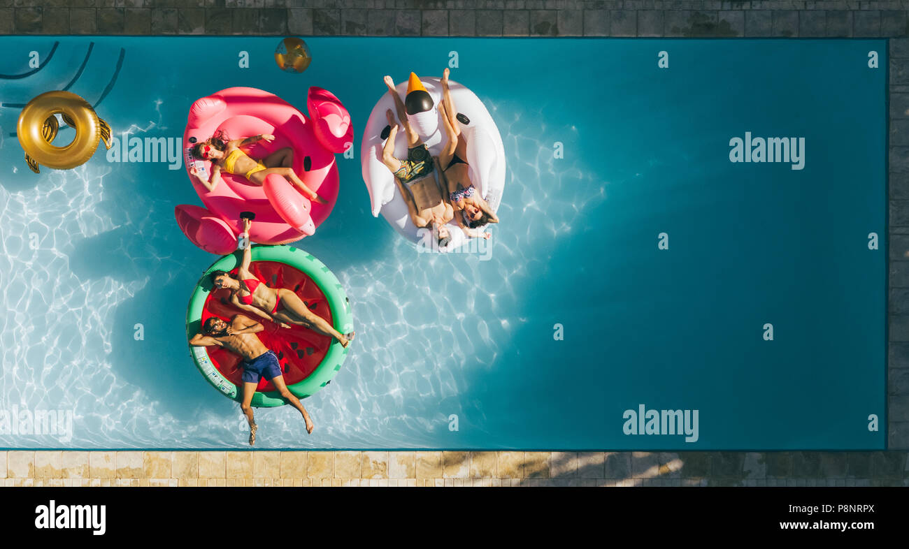 Aerial view of young people on summer vacation enjoying on fun inflatable floats in swimming pool. Group of friends relaxing on air mattresses in pool Stock Photo