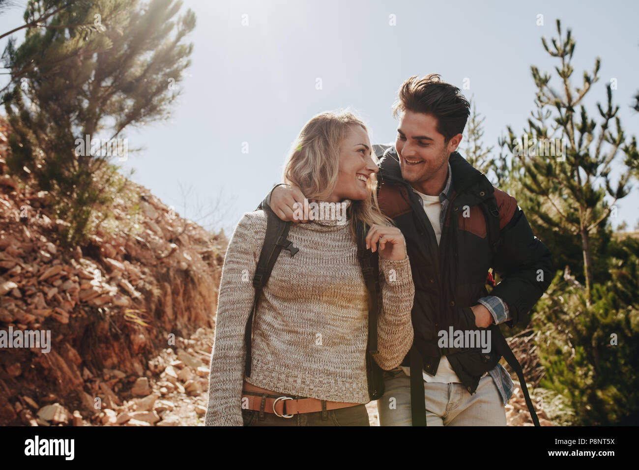 Couple in love on a mountain hike. Man and woman with backpack walking on mountain trail and looking at each other smiling. - Stock Image
