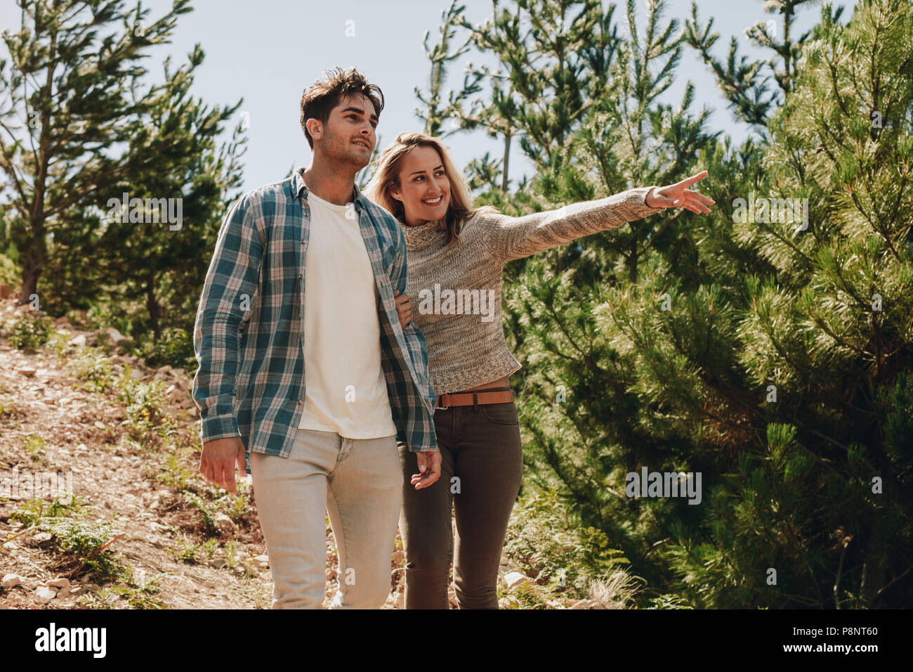 Young man and woman walking in mountain rail with woman pointing at a view. Couple looking at a beautiful view while hiking in nature. - Stock Image