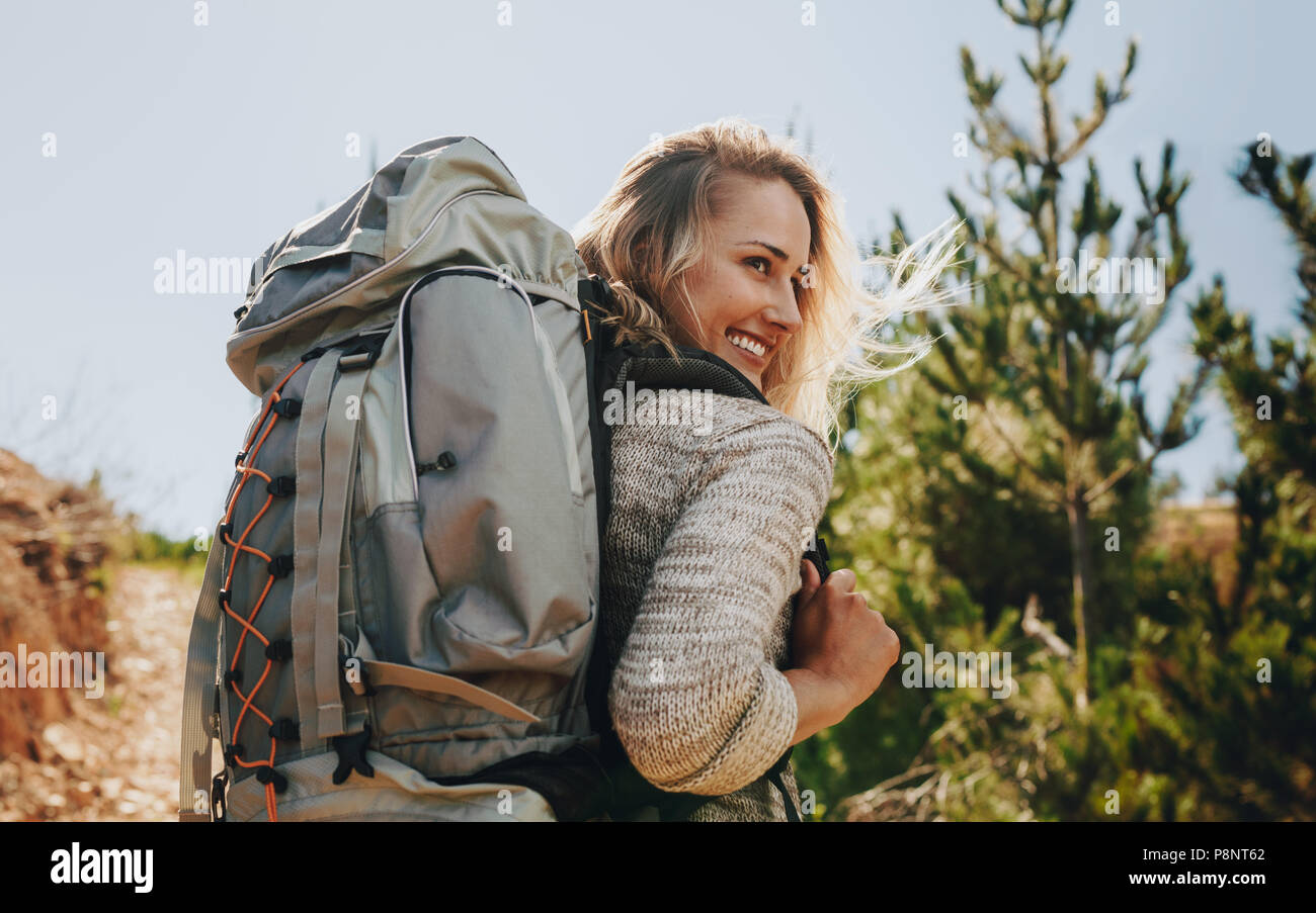 Rear view shot of smiling woman with backpack going on a camping. Caucasian female hiker on mountain looking away and smiling. - Stock Image