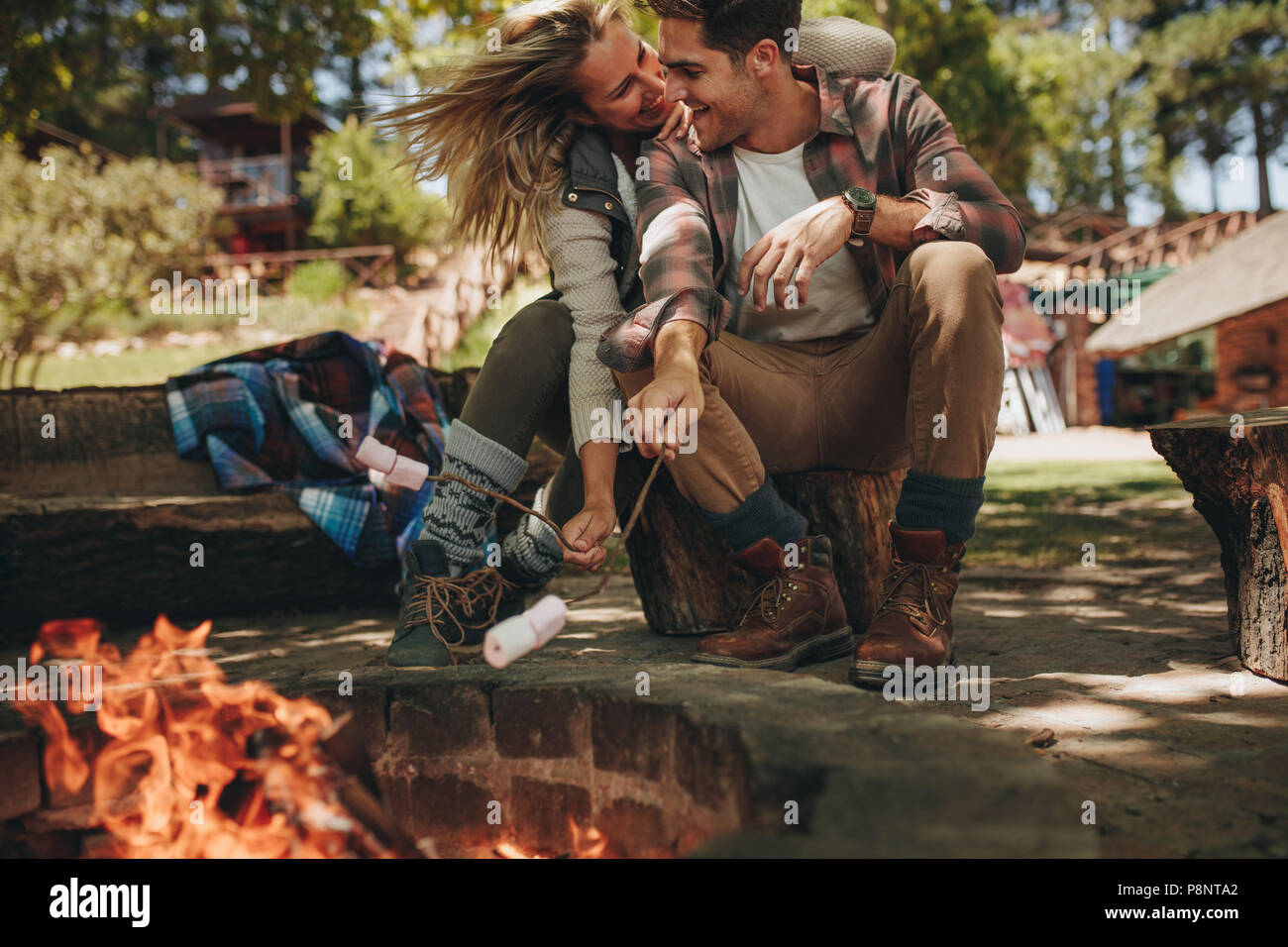 Romantic couple sitting by bonfire and roasting marshmallows on fire. Beautiful couple in love enjoying at campsite. - Stock Image