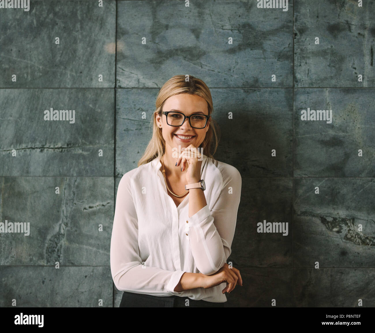 Portrait of beautiful young woman in formal wear standing against grey wall and smiling. Businesswoman with glasses looking at camera with hand on chi - Stock Image