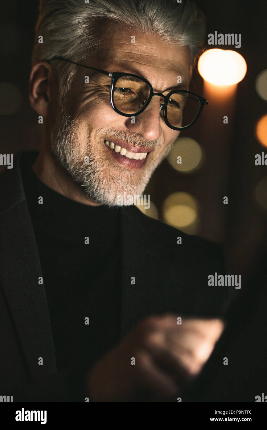 Close up of smiling businessman using digital tablet in office. Mature man working late night in office with tablet pc. - Stock Image