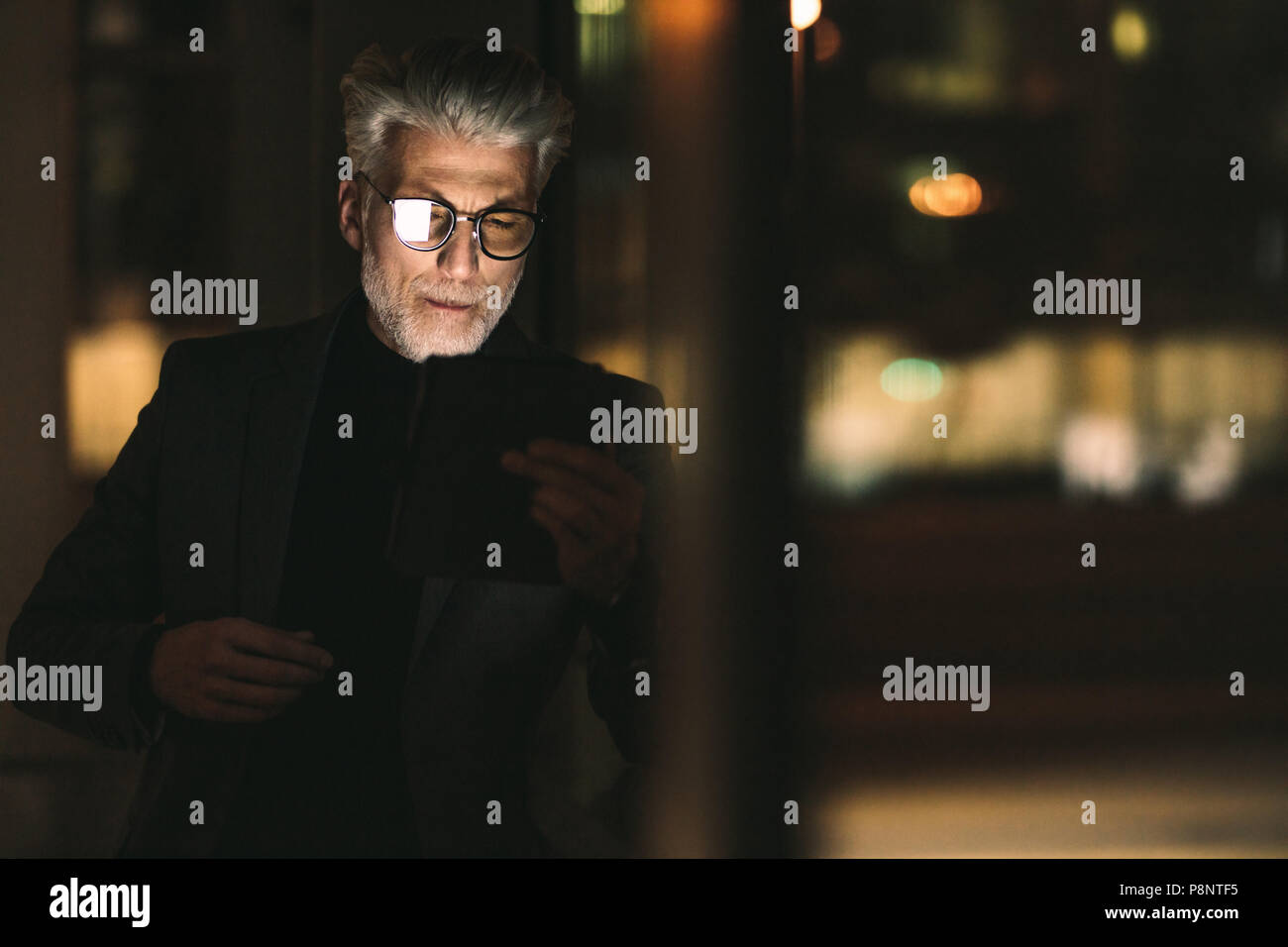 Senior businessman looking at digital tablet in office. Mature man during late working hours in office. - Stock Image