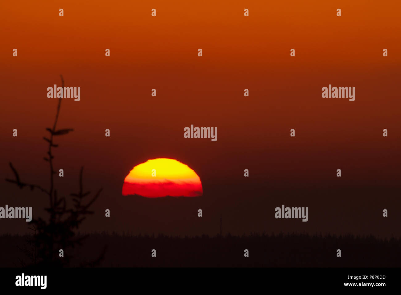 The setting sun appears to be flattened as a result of bending of the sunrays in this case amplified by the presence of volcanic ash in the atmosphere - Stock Image