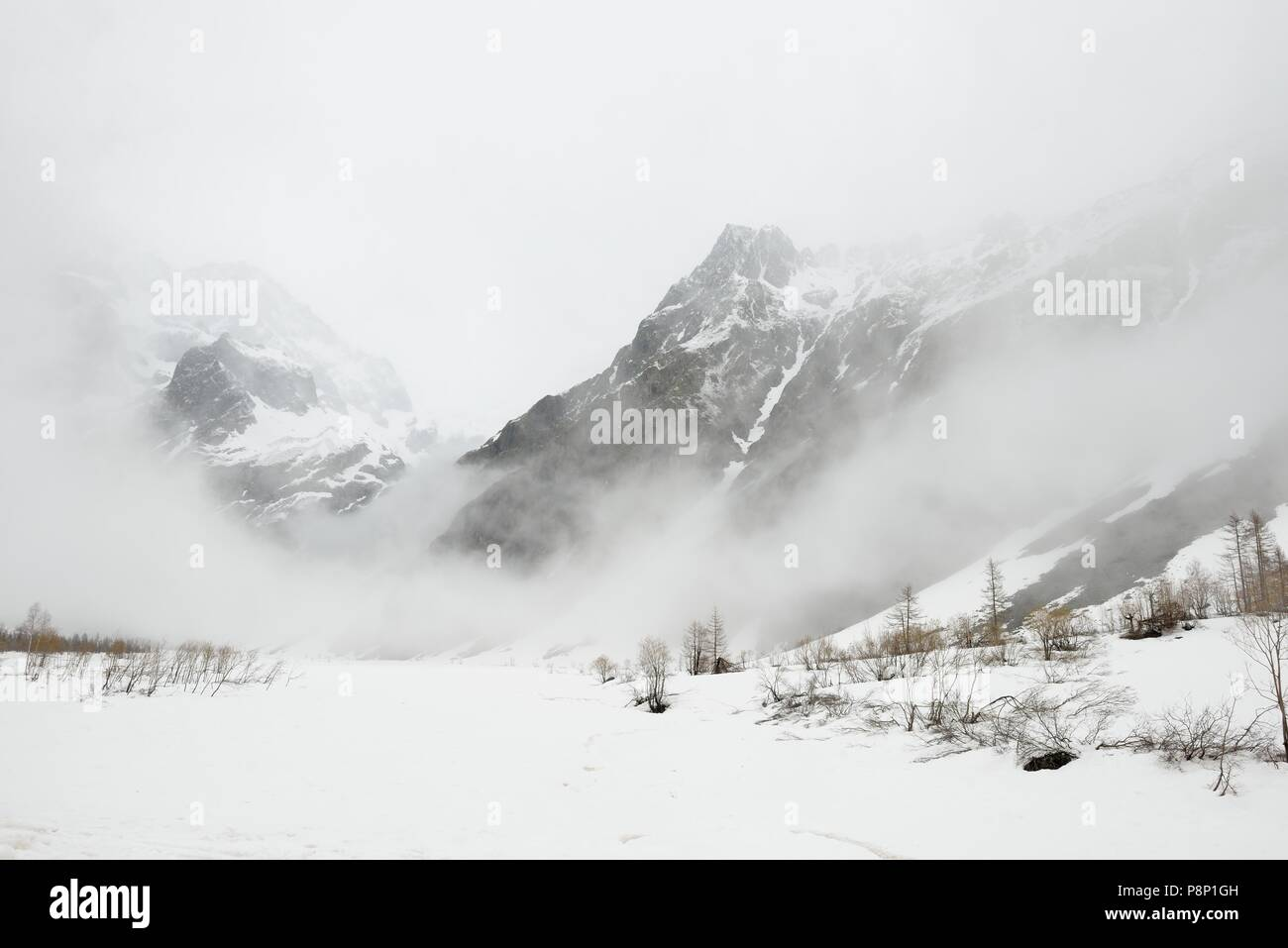Dramatic atmosphere during springtime in the French Alps with the snow melting and clouds hanging low - Stock Image