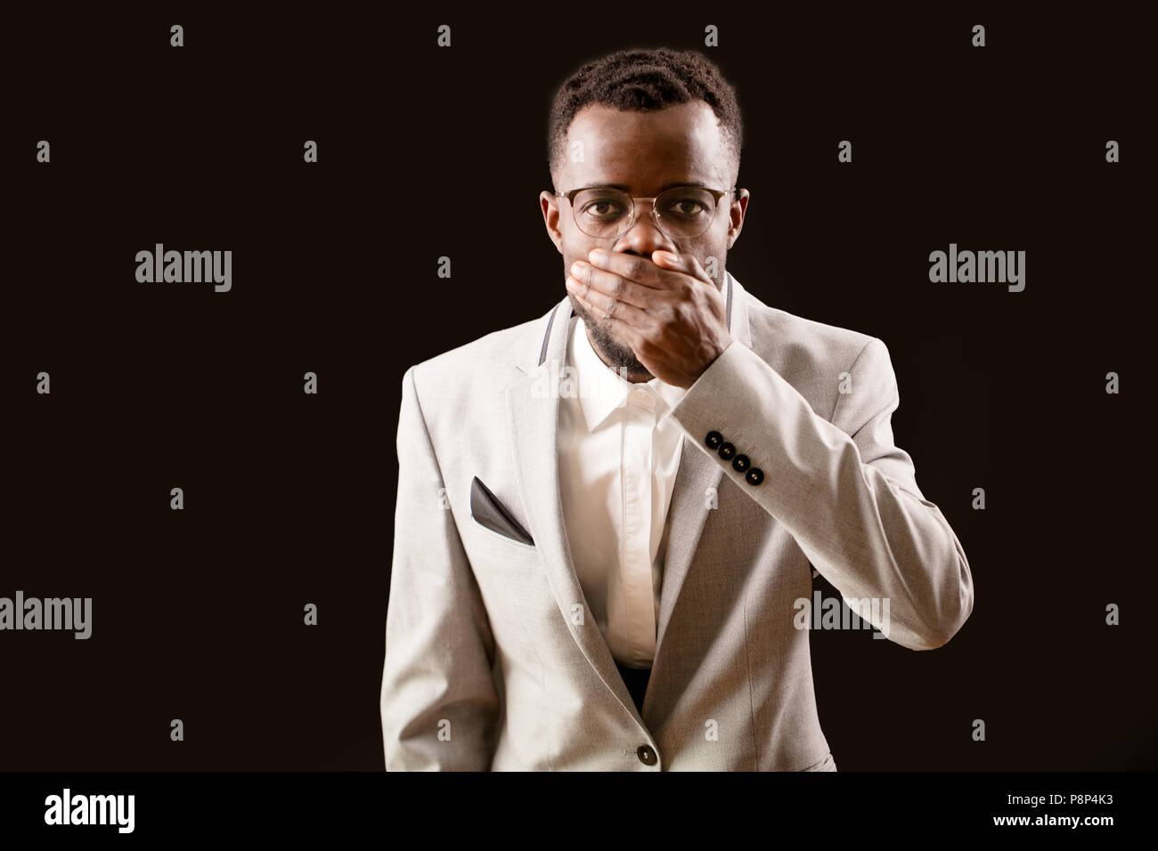 Young scared Afro man in glasses keeping his mouth closed by his hand on dark background. open-eyed man - Stock Image