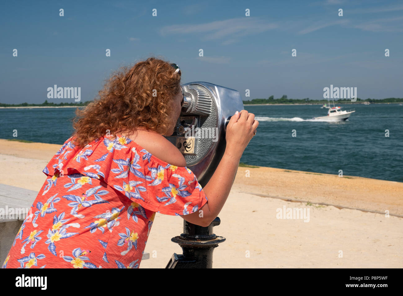 woman uses coin operated binocular to observe landscape, ocean, boats, beach scenes at the coast Stock Photo