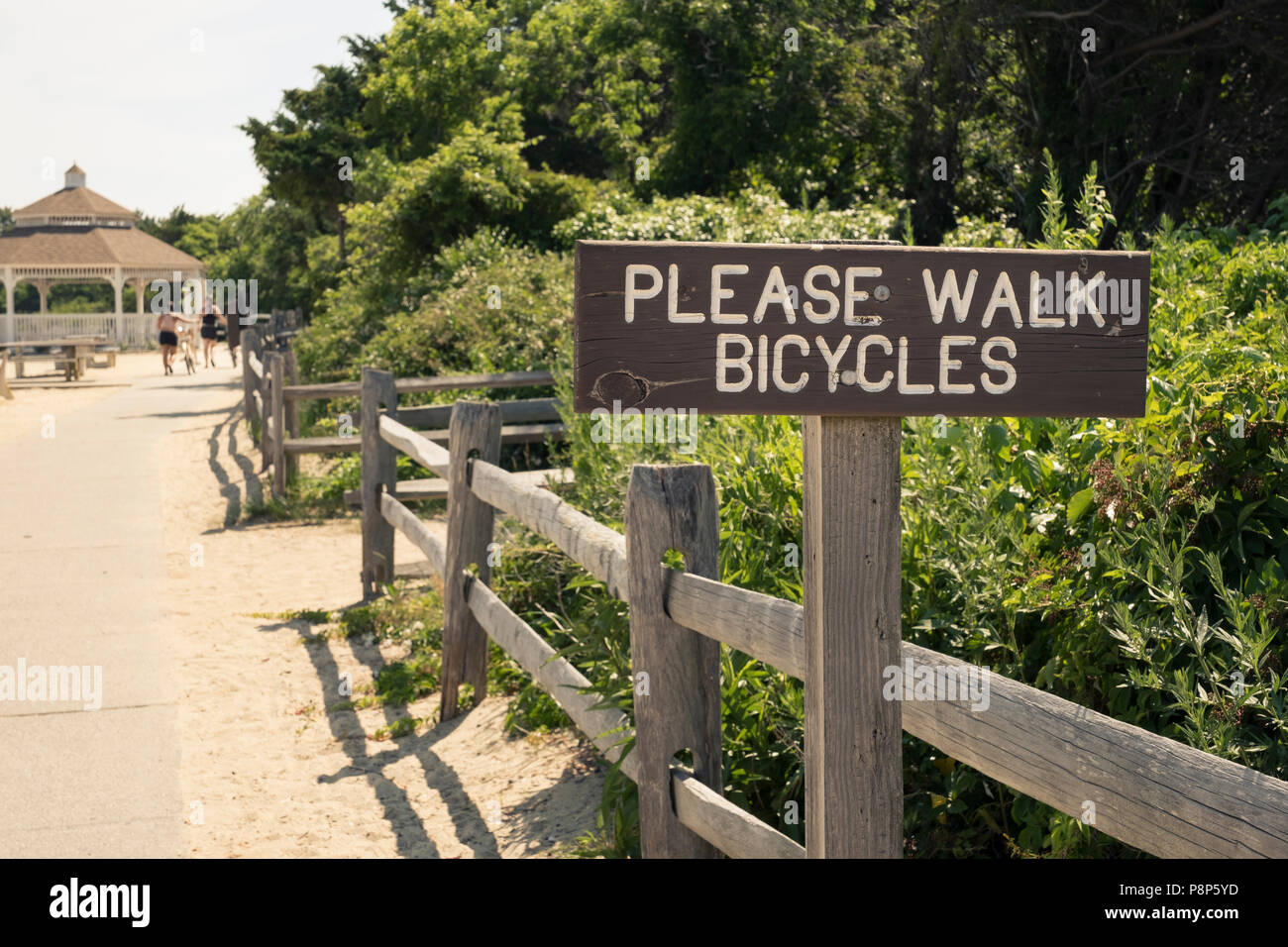 Signage to please walk bicycles on pedestrian path at a park Stock Photo