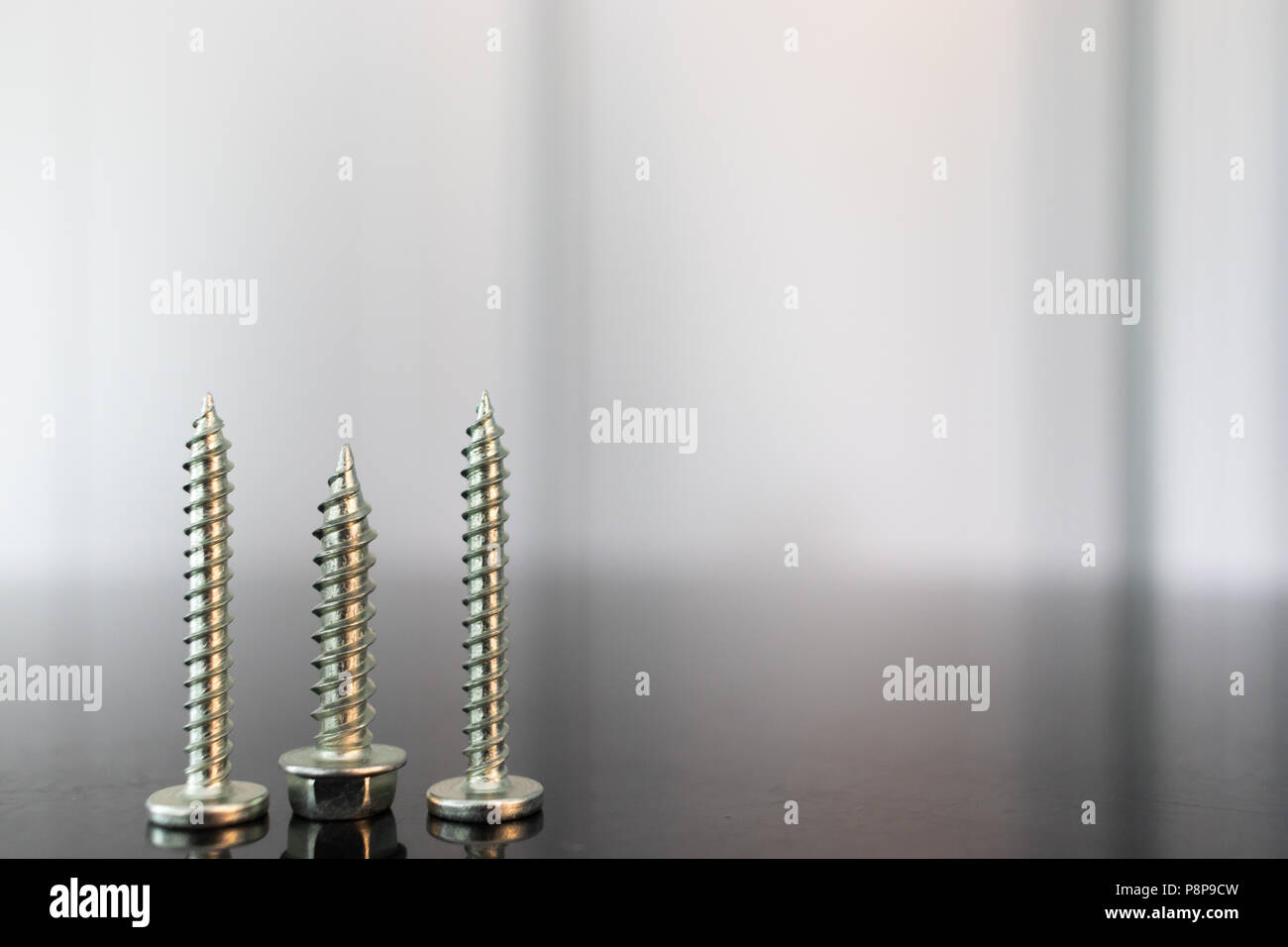 Roofing nails isolated on table with reflections - Stock Image