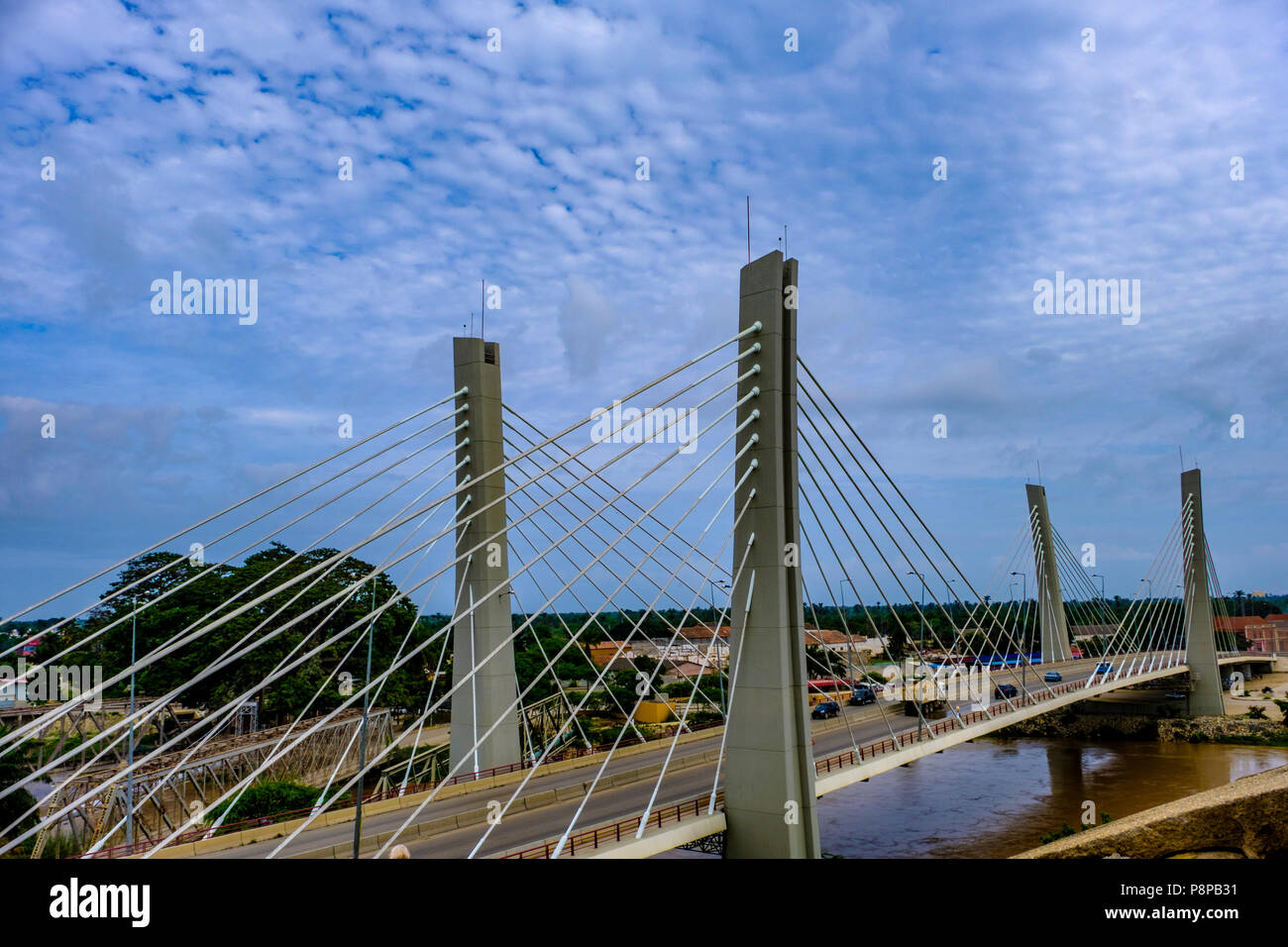 Traffic crosses modern suspension Bridge, 4 April, over Catumbela River linking cities of Benguela and Lobito in Angola with old bridge also visible - Stock Image