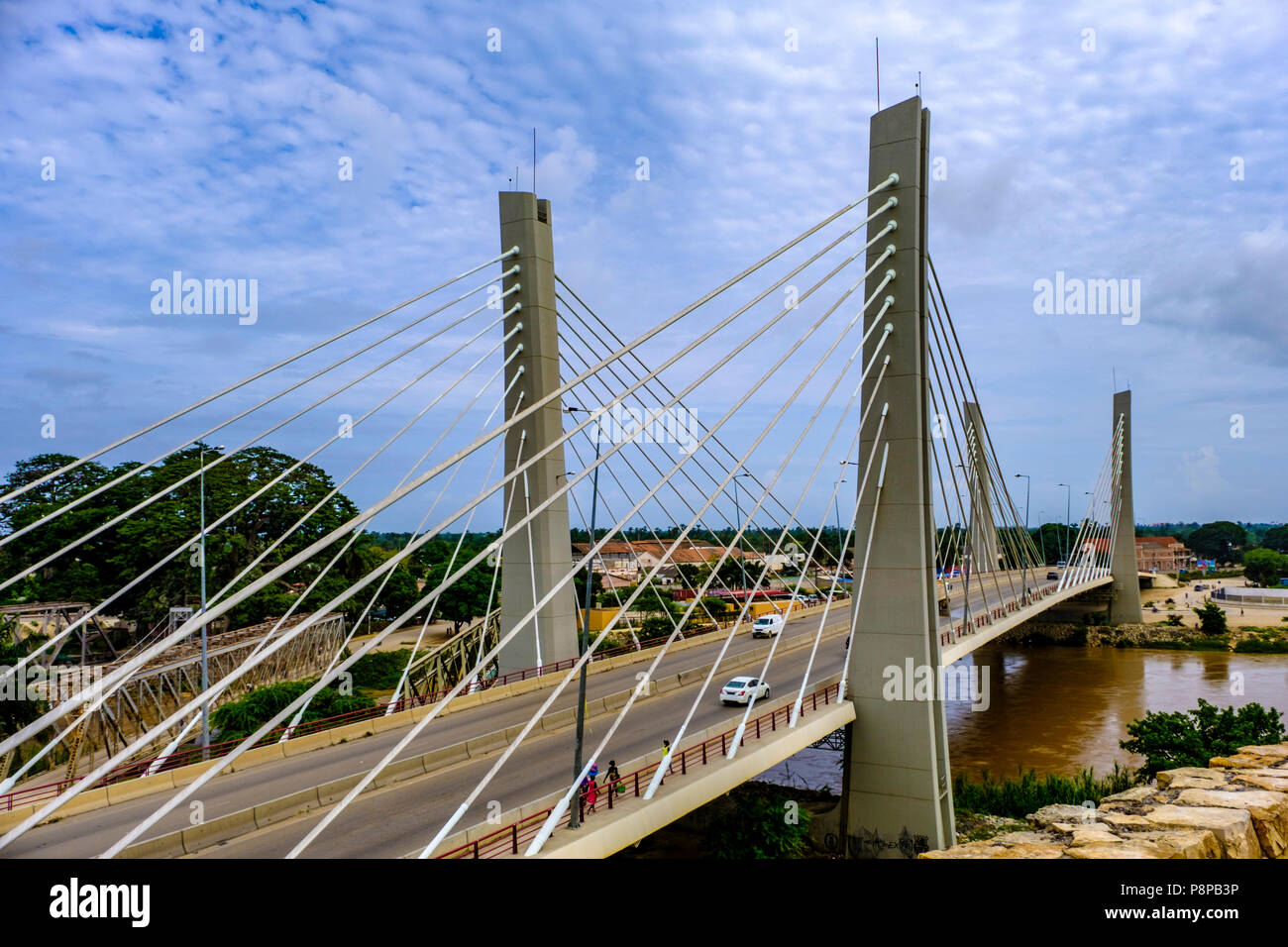 Traffic and pedestrians cross modern suspension Bridge, 4 April, over Catumbela River linking cities of Benguela and Lobito in Angola - Stock Image