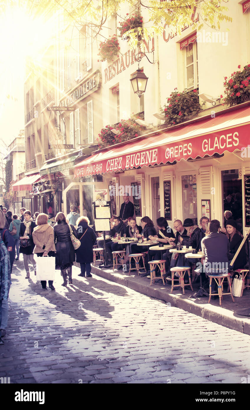 street in paris with cafe and parisians enjoying the sunny day - Stock Image