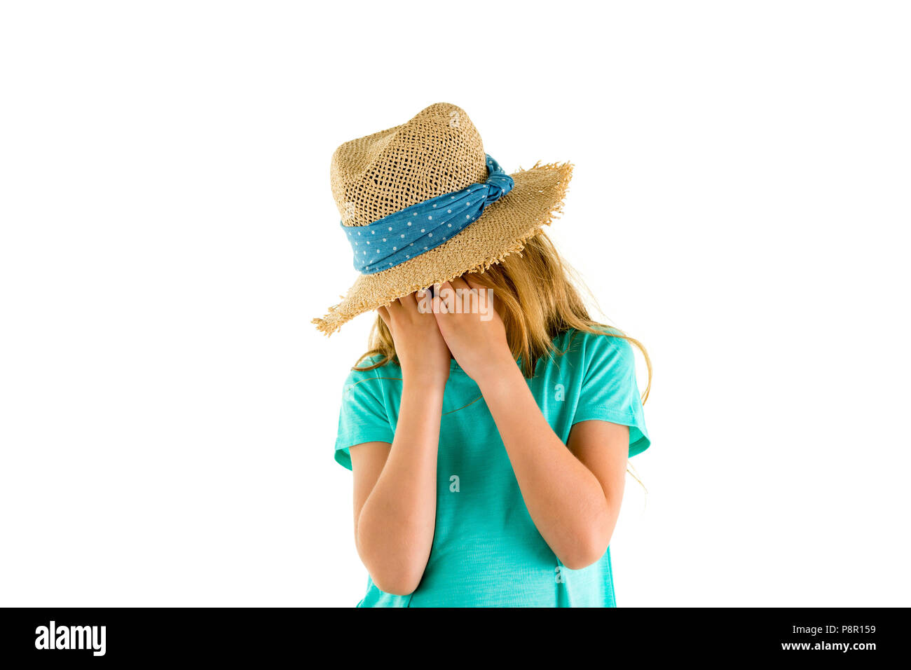 Upset little girl wearing a wide-brimmed straw sunhat sobbing into her hands as she covers her face isolated on white with copy space - Stock Image