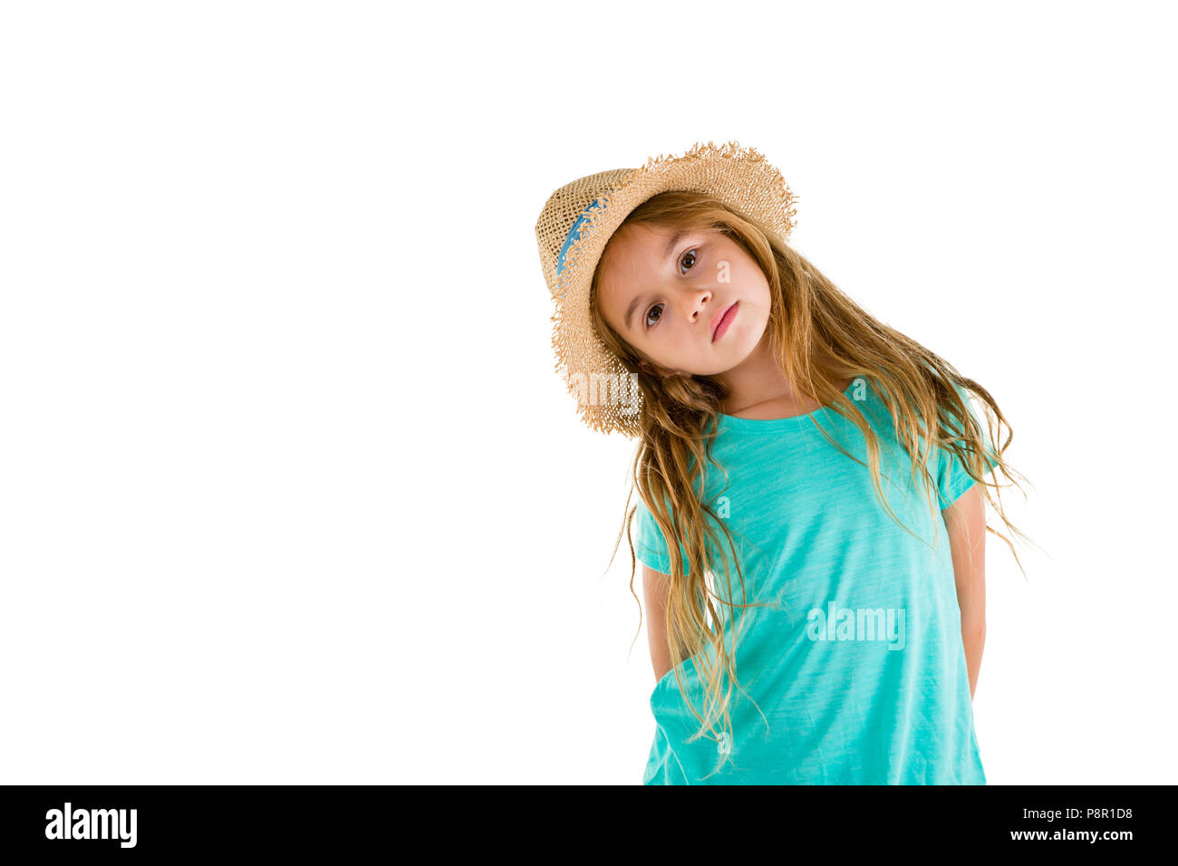 Cute little blond girl with long tousled hair wearing a straw hat tilting her head to the side as she stares at the camera with copyspace on white - Stock Image
