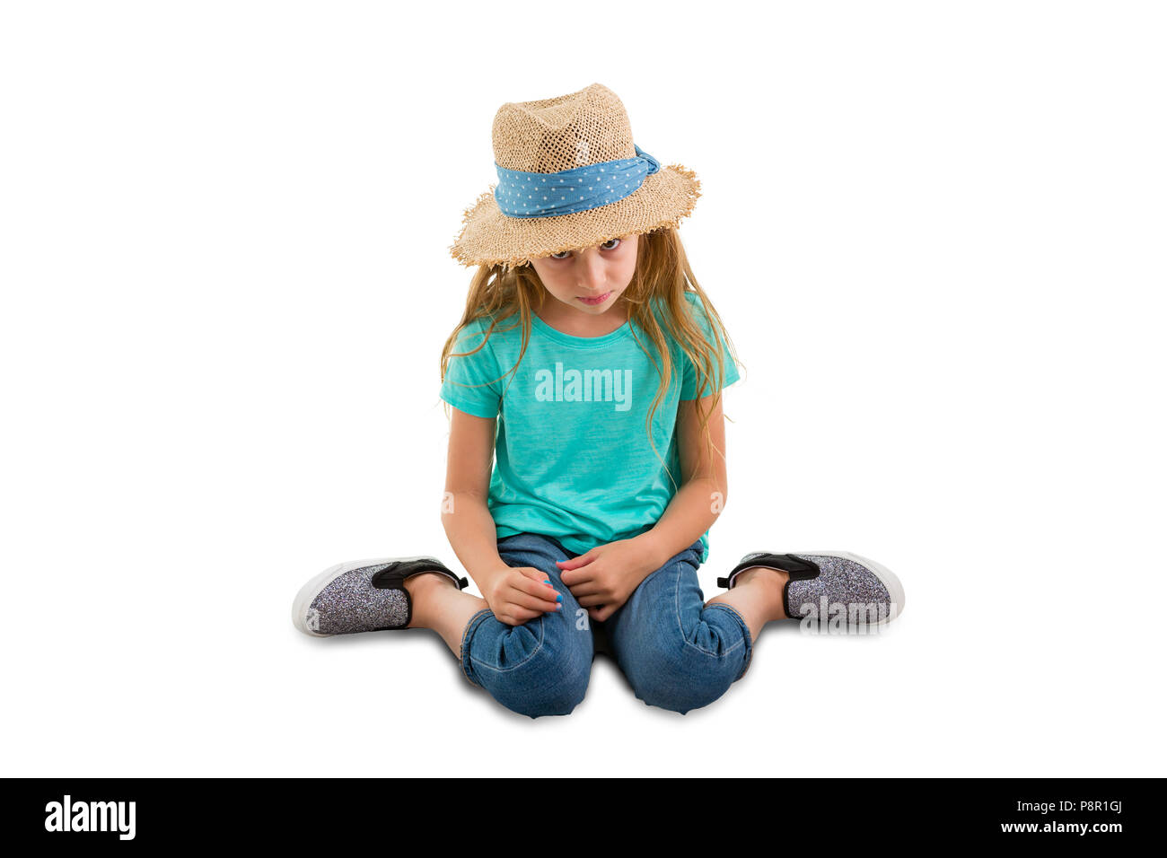 Guilty little girl sitting with her head bowed looking very contrite as she gazes down at the floor isolated on white with copy space - Stock Image