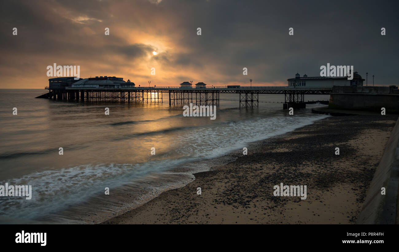 Cromer pier with clouds at sunrise, Norfolk, England - Stock Image